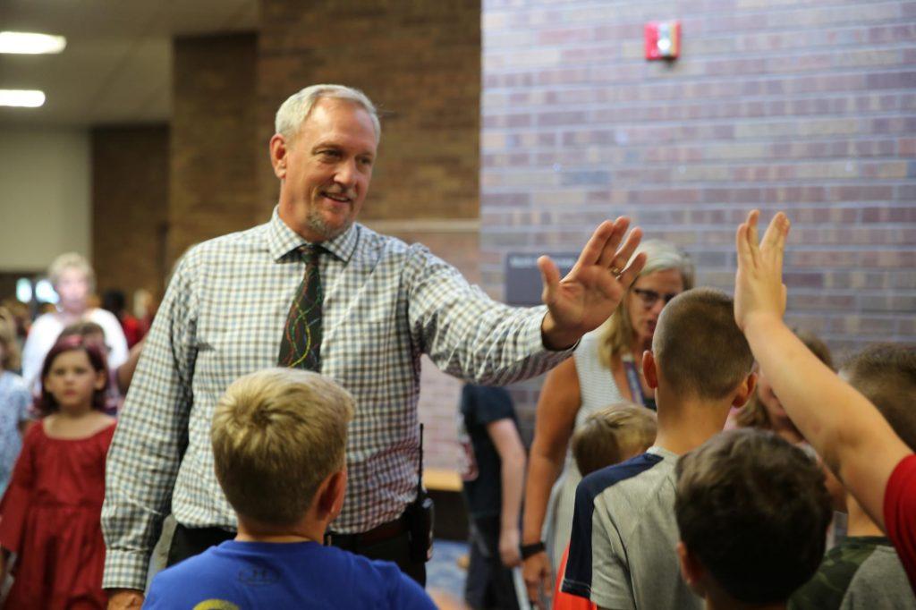 Principal Thompson high fives students