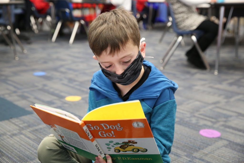 Child Reading Book on Floor